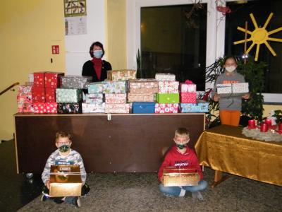 Unser Foto zeigt Kinder mit liebevoll gestalteten Päckchen und die Rektorin der Schule Annelies Rogler-Unglaub.