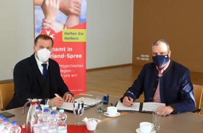 Uwe Kleiner, Regionalvorstand der Johanniter-Unfall-Hilfe, und Bürgermeister Sven Siebert unterzeichnen im Gemeindesaal den Vertrag.