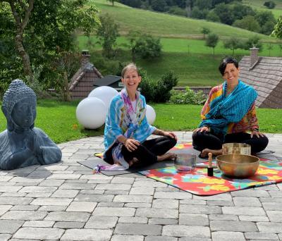 Auf dem Bild sieht man Birgit mit ihrer Yogakollegin Bettina im Schneidersitz vor einer Klagschale
