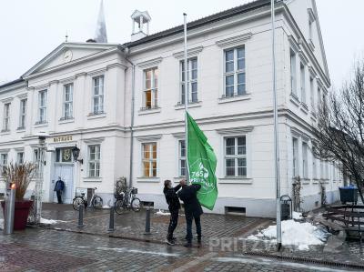 Bürgermeister Dr. Ronald Thiel hisst zusammen mit Jan Schulze die Fahne mit dem Jubiläumslogo. Foto: Beate Vogel/Video: Katja Zeiger