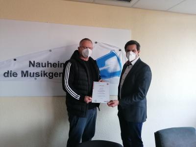 Bürgermeister Jan Fischer (rechts) übergibt Esmir Velic (links) die Ernennungsurkunde zum Sport-Coach des Hessischen Ministeriums des Inneren und für Sport. © Gemeinde Nauheim