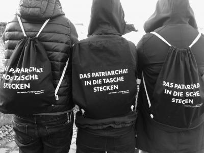 """Rückenansicht von drei Menschen, die Rucksäcke tragen auf welchem """"Das Patriarchat in die Tasche stecken"""", steht"""