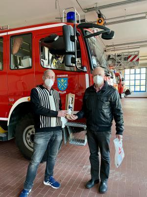 Burkhard Scherzer vom Stadtverband der Freiwilligen Feuerwehr Seelow e.V. übergibt Jubilar Bernd Kietzer Präsent für die 125. Blutspende