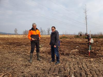 Auf dem Bild sehen Sie Hans-Gerrit Lüdicke und Fachbereichskoordinator Lars Obermann vor den Flächen, wo Arbeiter gerade dabei sind, die Anpflanzungen vorzunehmen.