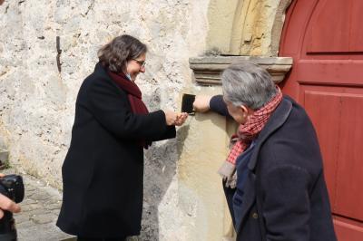 Frau Pfarrerin Breustedt befestigt gemeinsam mit dem Vertreter des Kulturrades der EKD die Projektplakette an der Scherbdaer Kirche.Gemeinsam setzen die Projektbeteiligten einen Ahornbaum als Zeichens des Werdens und Wachsens des Projektes.