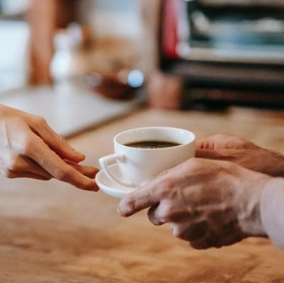 Man sieht die Hände von einer Person, wie sie einer anderen Person eine Tasse Kaffee gibt; Foto von Gary Barnes von Pexels