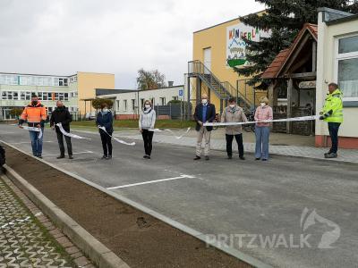 """Das Band wird durchschnitten, damit ist der Parkplatz vor der Kita """"Kinderland"""" offiziell übergeben. Foto: Beate Vogel"""