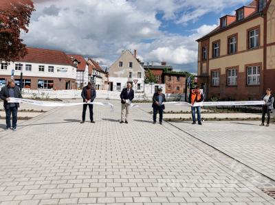 Mit einem Schnitt durch das Band gaben Bürgermeister Dr. Ronald Thiel und die Baubeteiligten den neu gestalteten Postplatz offiziell frei. Foto: Katja Zeiger