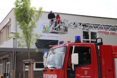 Von der Drehleiter der Freiwilligen Feuerwehr Dörnigheim aus enthüllte Bürgermeisterin Monika Böttcher das neue Hausschild des Kinder- und Familienzentrums Eichenheege. Foto: Stadt Maintal
