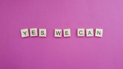 Scrabble Steine auf pinken Untergrund mit Yes we can!