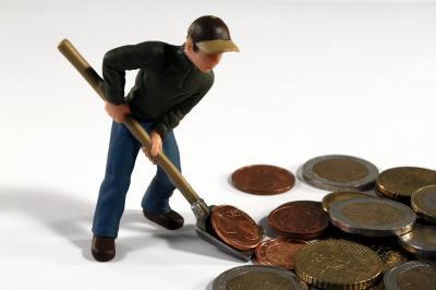 Eine kleine, männliche Figur schaufelt Geldstücke.
