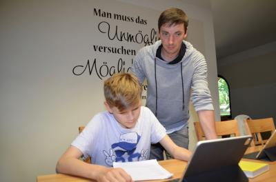 Dominik lernt am Laptop. Der Erzieher Tobias Walter schaut ihm über die Schulter. Foto: Andreas Staindl