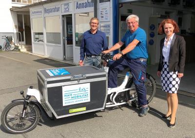 Markus Röder (links) und Bernd Schickling von der Beckl Karosserie + Lack GmbH & Co. KG in Maintal führen Wirtschaftsförderin Anke Prätzas das neue E-Lastenrad vor.  Foto: Stadt Maintal