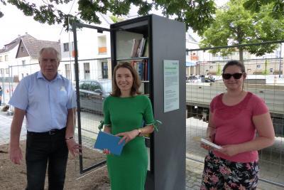 Bürgermeisterin Monika Böttcher und Erster Stadtrat Karl-Heinz Kaiser stöberten schon mal in der Auswahl des neuen Bücherschranks in Bischofsheim. Johanna Kächelein (rechts) wird die kleine Bibliothek als Patin betreuen.