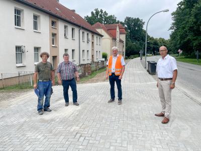 Wieder ein Stück Gehweg fertig: Bürgermeister Dr. Ronald Thiel (r.) und weitere Vertreter von Stadt und Baufirma übergaben den neu gestalteten Abschnitt in der Kyritzer Straße. Foto: Jenny Miersch