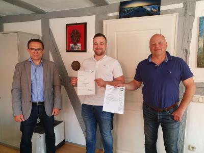 Bürgermeister Jörg Schützeberg (r.) und Ausbilder Lars Obermann (l.) bei der Übergabe des Arbeitsvertrages an den Verwaltungsfachangestellten Pascal Göhl.