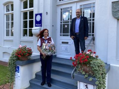 Bürgermeister Michael Hook überreicht Manuela Burkhardt einen Blumenstrauß