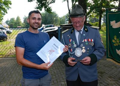 Georg Zörner (links), Gewinner des Spanferkels. Überreicht wurde der Gutschein von Thomas Hustan, Vereinsvorsitzender (rechts)