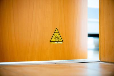 Der neongelbe Aufkleber wird im unteren Drittel der Kinderzimmertür angebracht.