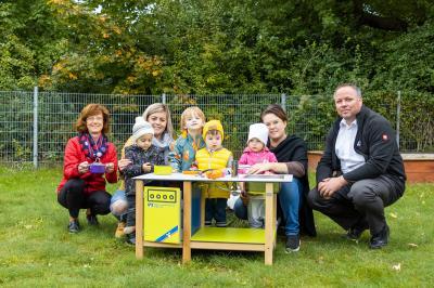 """Anke Hahn (li.) und Ronny Löwe (re.) überreichen der Kindertagesstätte """"Schlaufüchse"""" die neue Matschküche   Foto: Volks- und Raiffeisenbank Prignitz"""