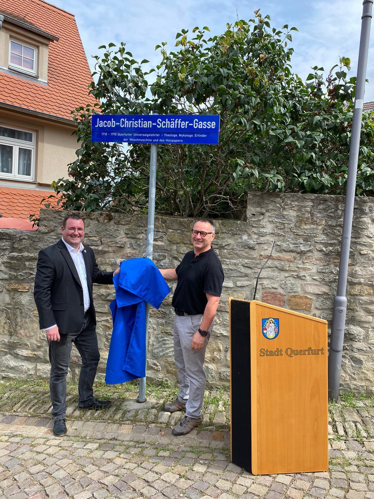 Gemeinsam mit Tierarzt Gunnar Schwarz enthüllt Bürgermeister Andreas Nette das Zusatzschild an der Christian-Jacob-Schäffer-Gasse