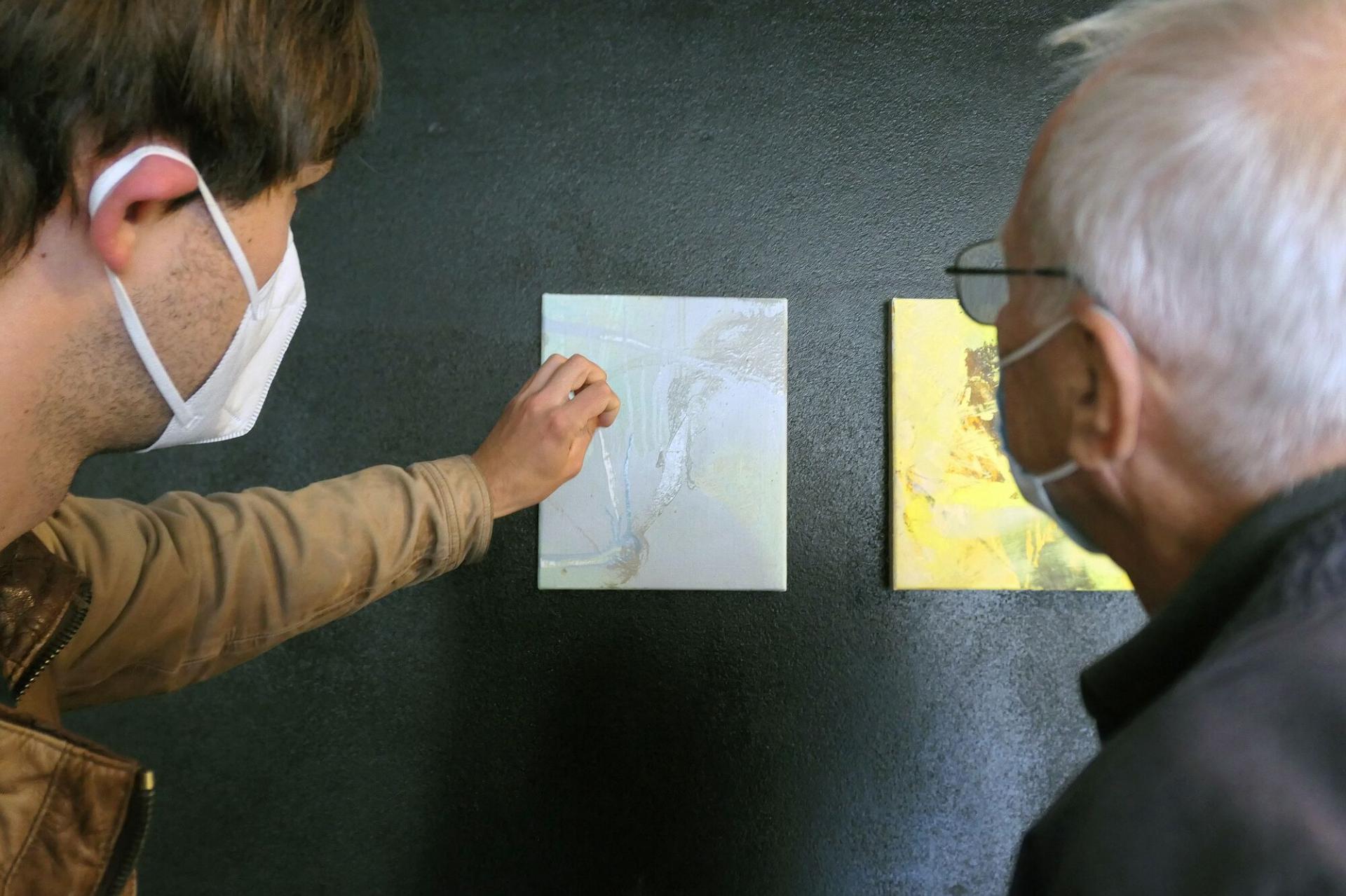 Franz Rentsch (l.) erklärt Peter Löwe wie dieses Bild entstanden ist. Unter anderem ließ er es einen Tag im Regen hängen, um zu beobachten, wie sie die Farben dadurch verändern. Foto: Ingrid Hoberg
