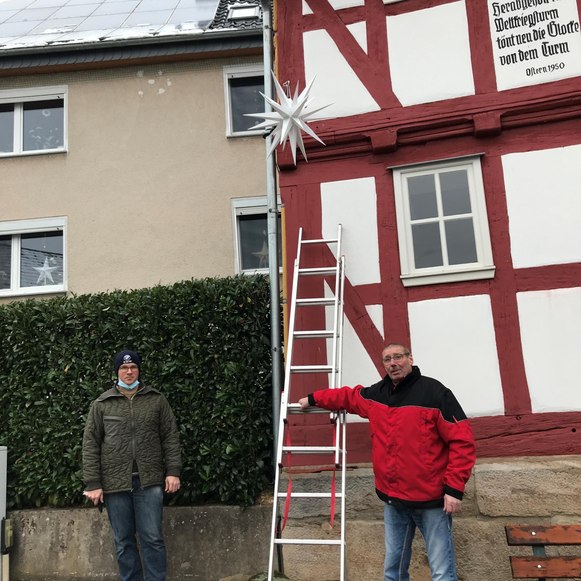 """Ortsvorsteher Kay Bube (links), Ortsbeirats-Mitglied Norbert Wenzel (nicht im Bild) und Volkstanz-Mitglied Horst Habermehl (rechts) montierten den Stern am """"Dom"""" von Malkomes."""