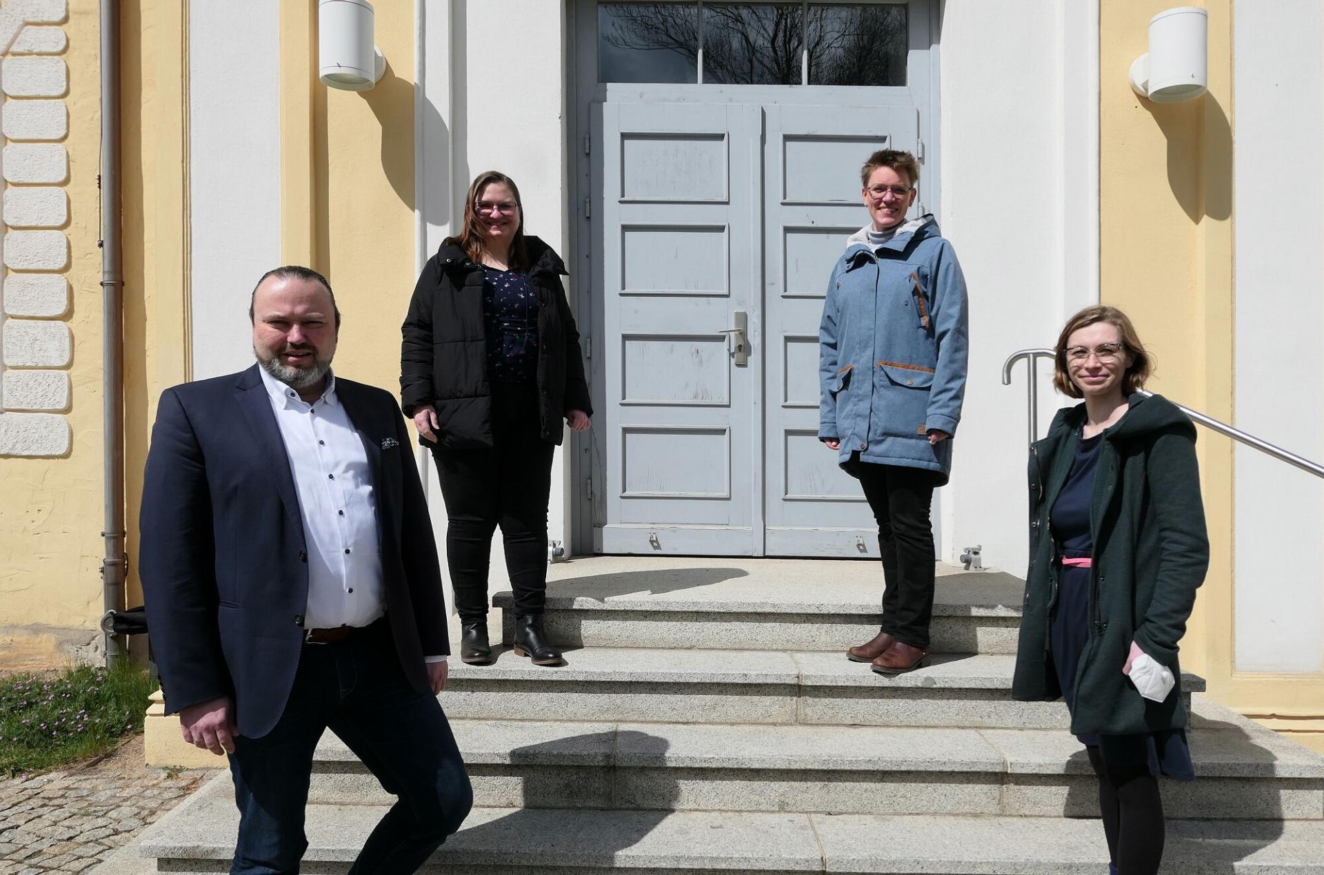 Kulturdezernent Stefan Wichary, Madline Riemer, Janina Schneider und Projektleiterin Marianne Wenzel (v.l.n.r.) vor dem Lübbener Schloss.