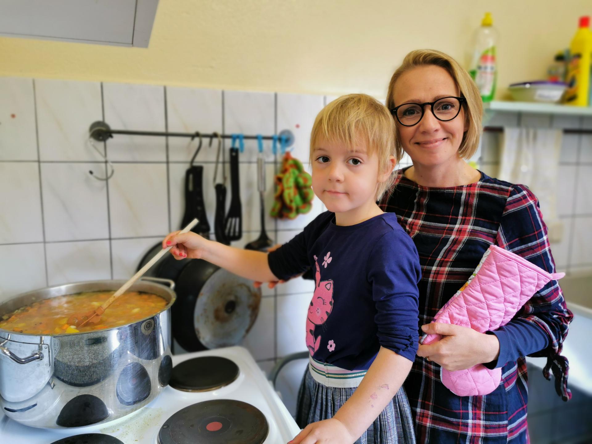Inna (5) und Kita-Leiterin Stefanie Jungwirth kochen Kürbissuppe.