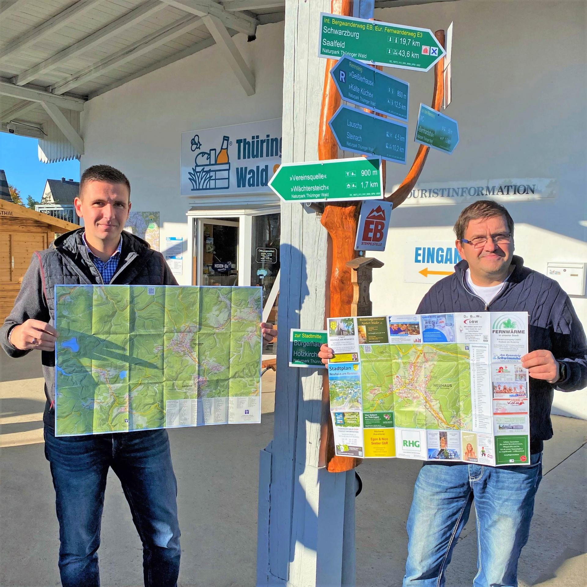 Geschäftsführer Jörg Seifert (links) und Bürgermeister Uwe Scheler (rechts) mit dem neuen Stadtplan vor dem Thüringer Wald Shop mit Touristinformation in der Neuhäuser Bahnhofstraße 10