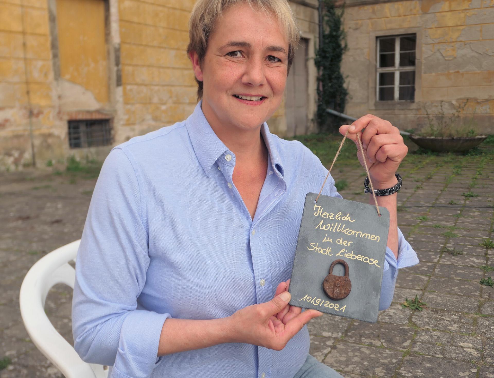 Lieberoses Bürgermeisterin Petra Dreißig mit ihrem Begrüßungsgeschenk für den Käufer des Schlosses. Foto: Ingrid Hoberg