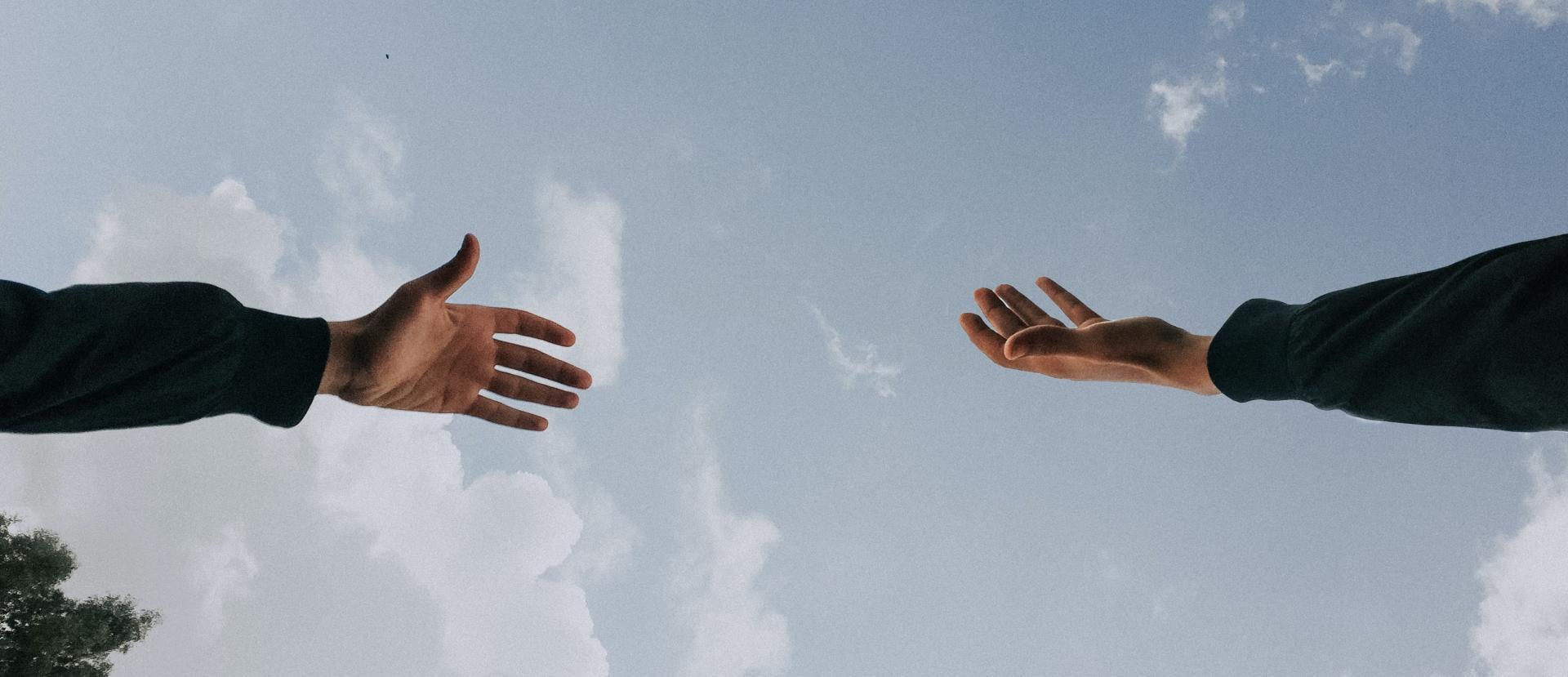 Header-Bild: Hände, die aufeinander zu gehen, gereicht werden