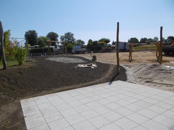 Terrasse Sandspielfläche und Schaukelgerüste.