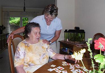 Pflegekraft hilft einer alten Dame