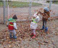 Kinder spielen mit Laub