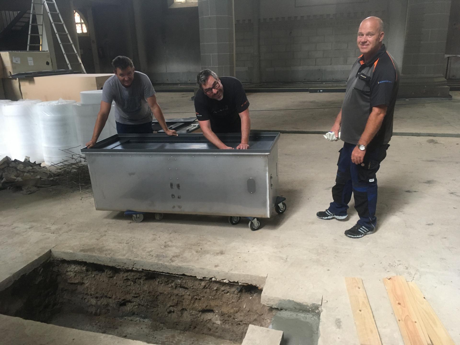 Bild IV zeigt Herrn Jauch, Herrn Müller und Herrn Reinhardt aus Rudolstadt beim Auspacken einer Wärmestationseinheit