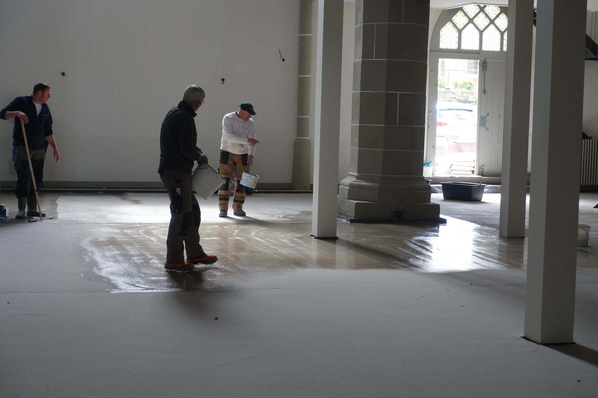 """Der Estrichverleger Matthias Kunde bereitet mit seinen Mitarbeitern den Estrichboden vor mit Quarzsand, der nach 24 Stunden wieder abgefegt wird- so wird der Boden """"griffiger"""" und die Oberfläche insgesamt erhöht zur besseren Haftung."""