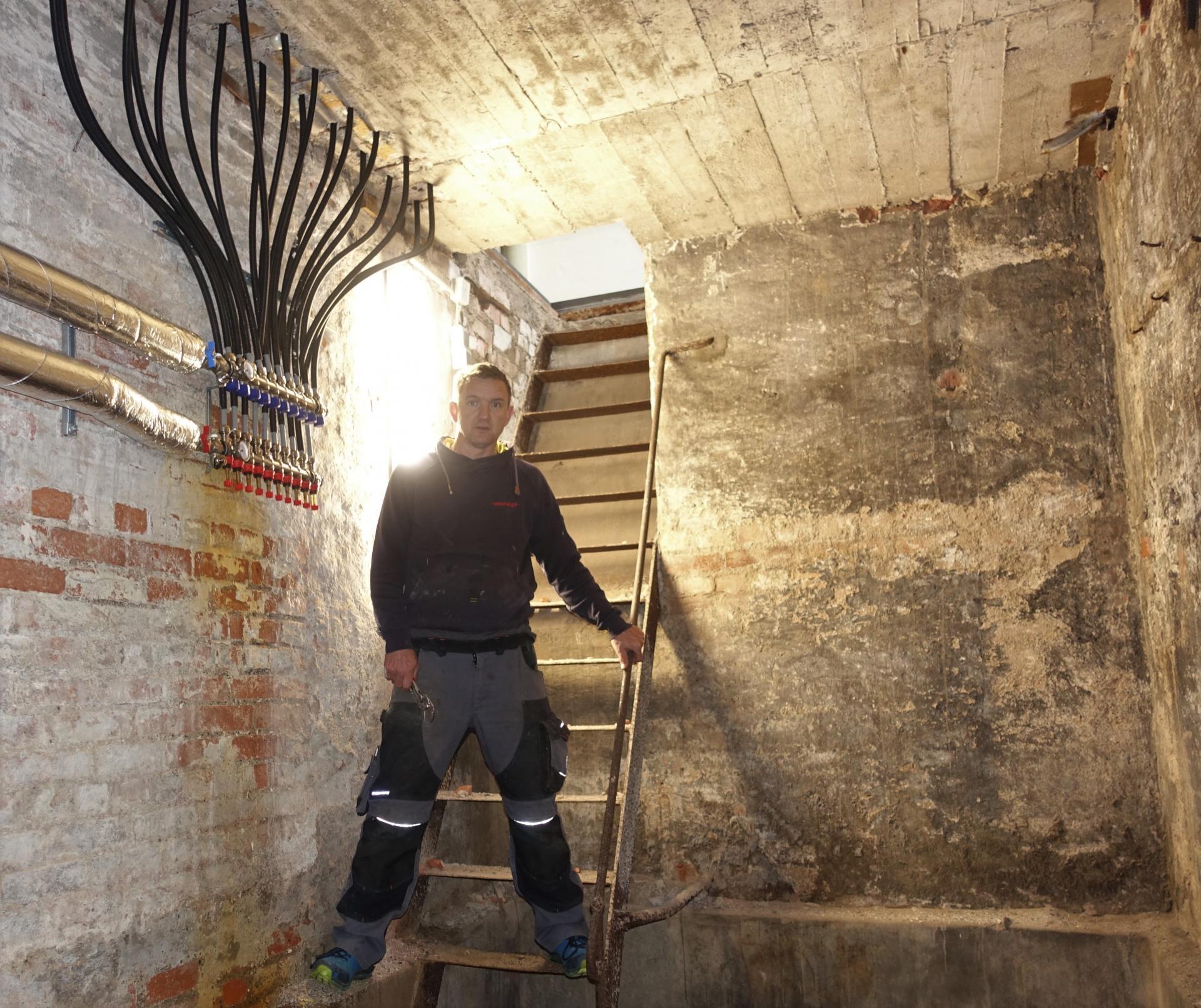 Herr Jauch im Keller unter der Kinderkirche; rechts von ihm kommen die Flächenheizungsschläuche aus dem Chorraum zusammen.