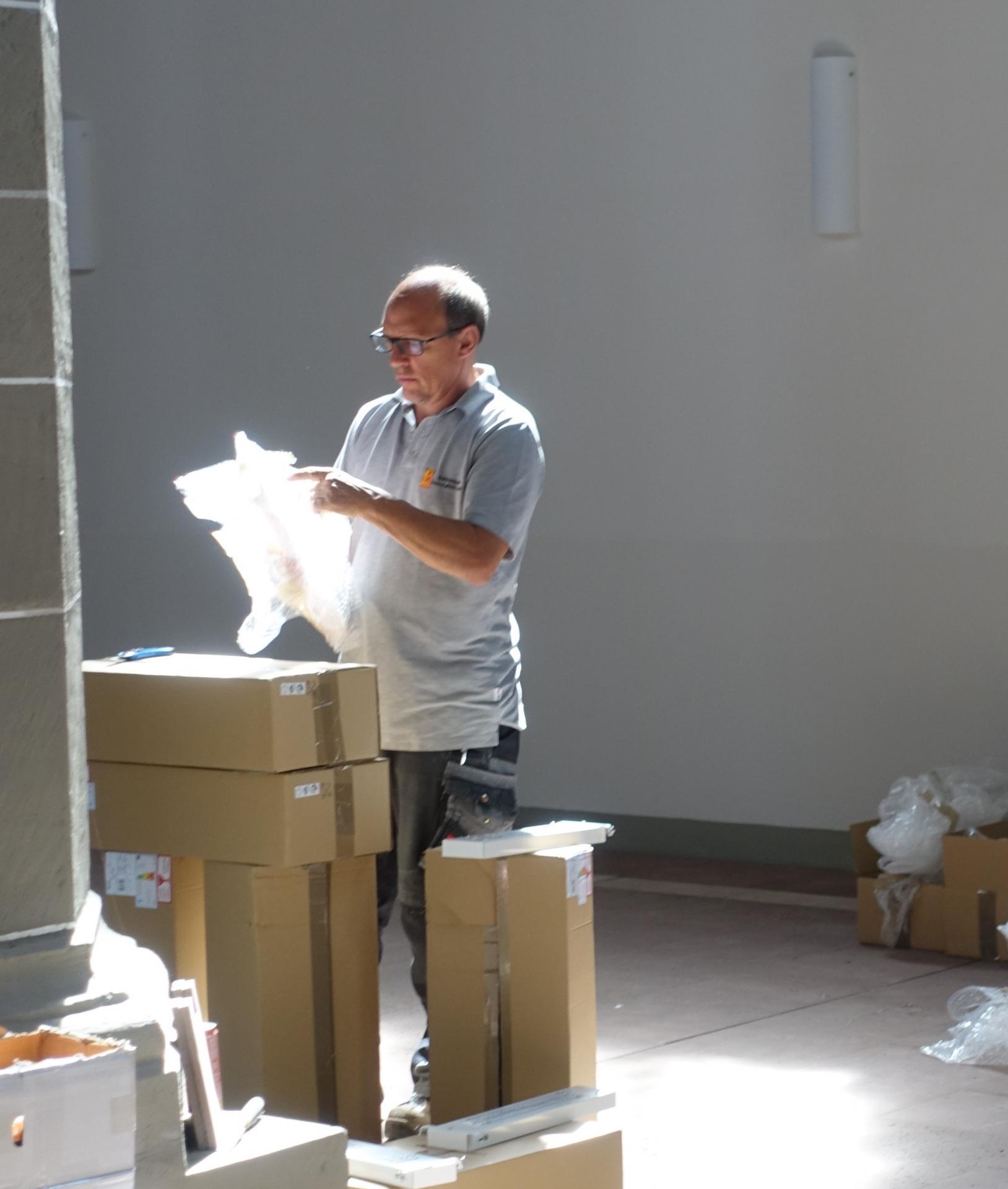 H.Wendt von der Fa. Dette-Kulfürst packt die Lampenschirme aus, die mit weißen Handschuhen auf die Leuchtdioden der Basisplatten befestigt werden.