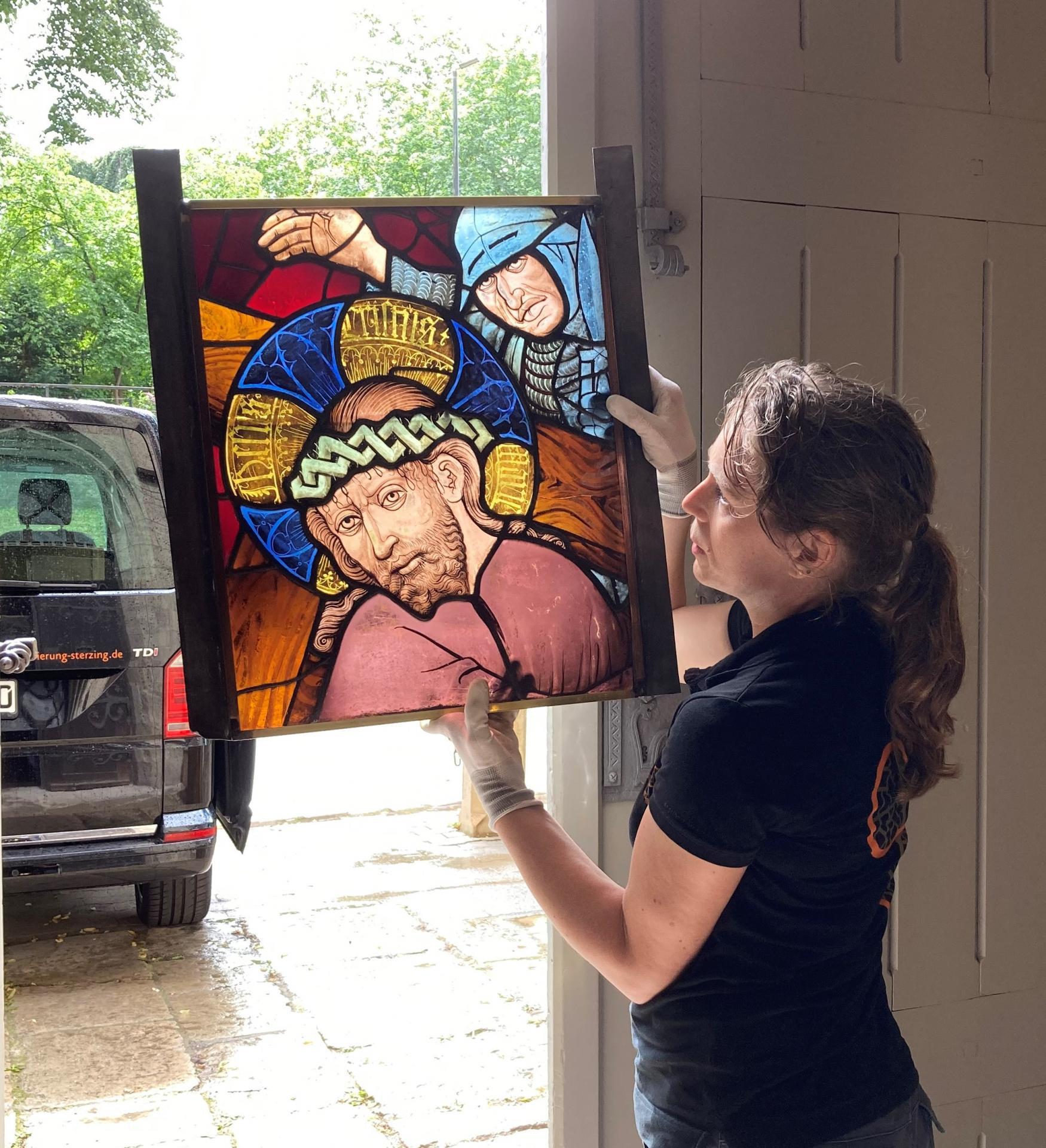 Nicole Sterzing, von einem Regenguss überrascht, zeigt ein Fensterfeld im Durchlicht