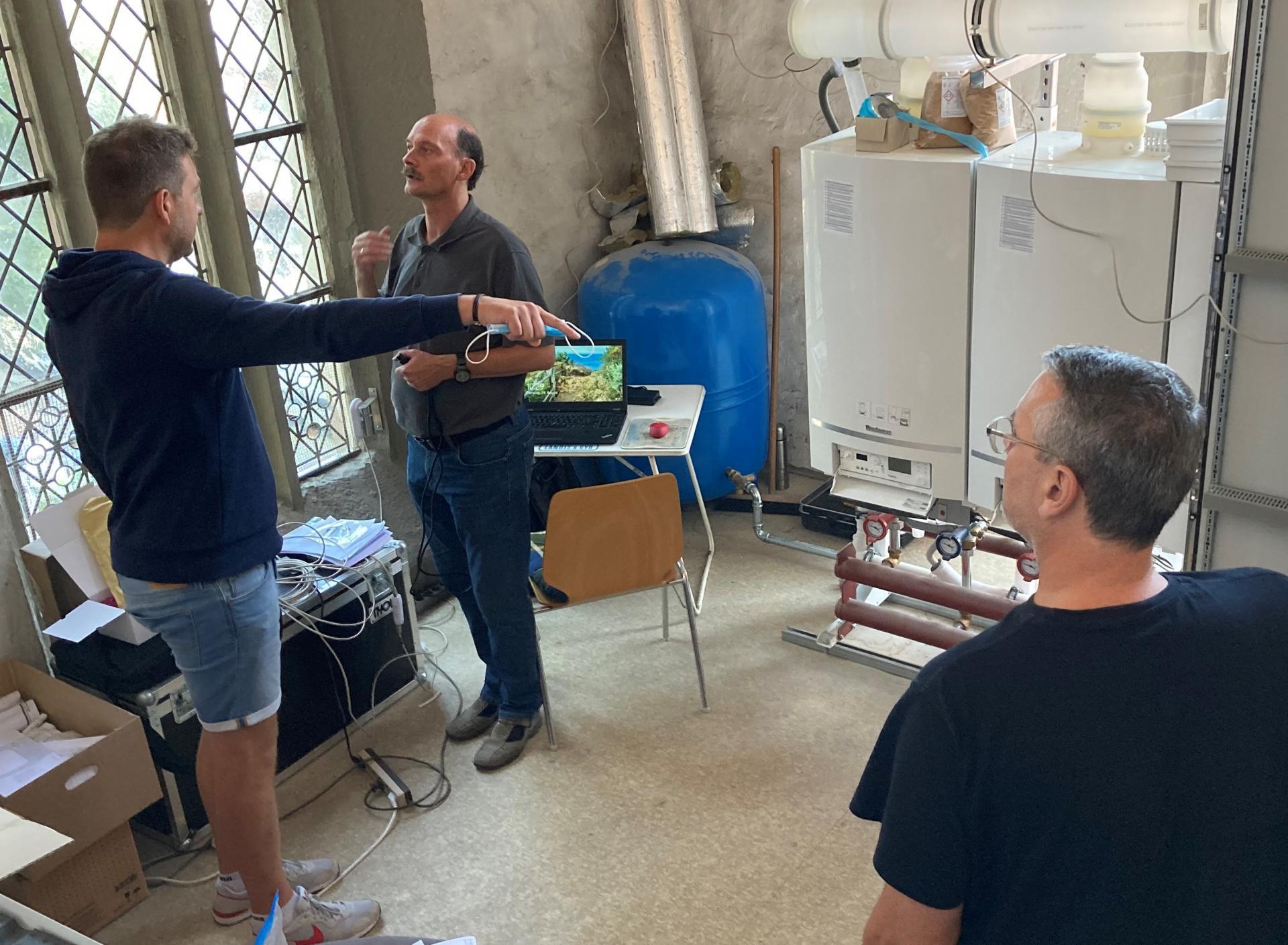 Wir befinden uns im Heizungsraum mit den drei Heizkesseln. Herr Schneider, Benjamin Dippel und Sönke Ehrhardt hören zu und ergänzen.