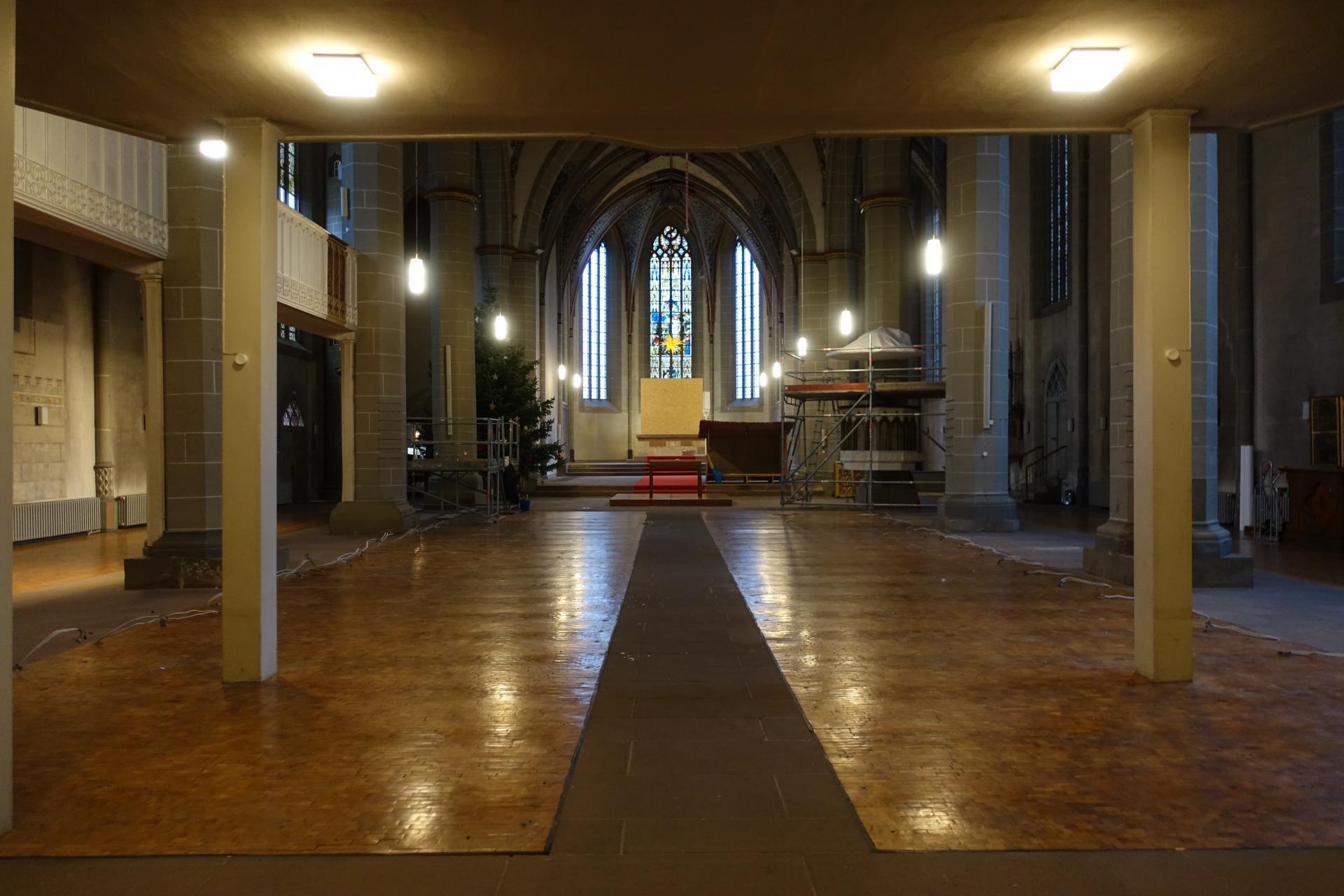 Kirche ohne Bänke mit Gerüst bei der Taufe, eingerüstete Kanzel und eingehauster Altar.