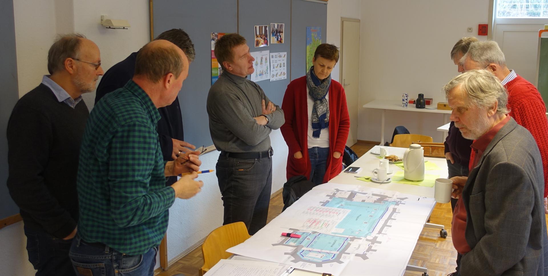 Herr Baumann, der den Anwesenden seinen Plan mit Bezug auf die Erkenntnisse der Beheizungssimulation erklärt