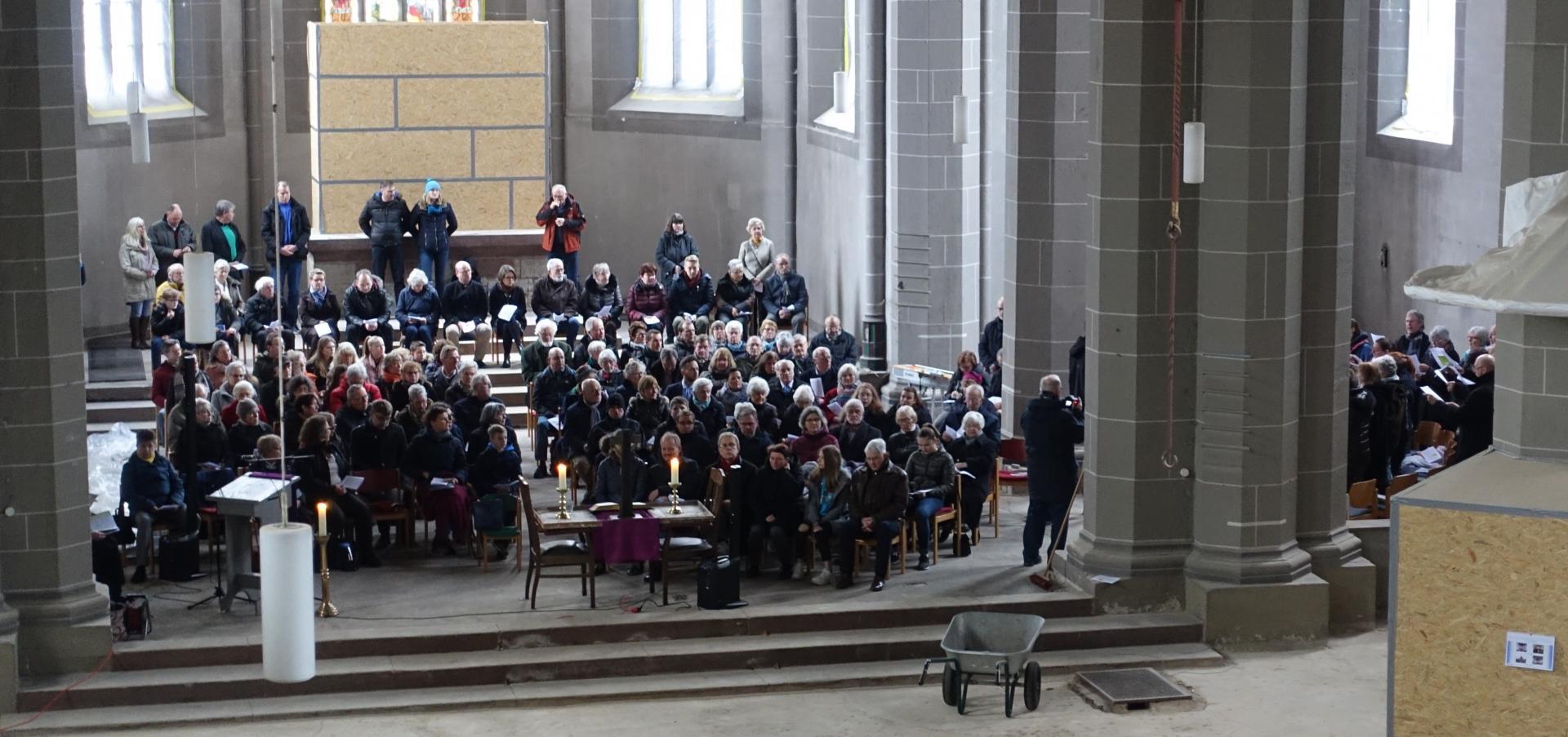 Die Gemeinde hat Platz genommen und die Kantorei wird hocharmig von Benjamin Dippel dirigiert