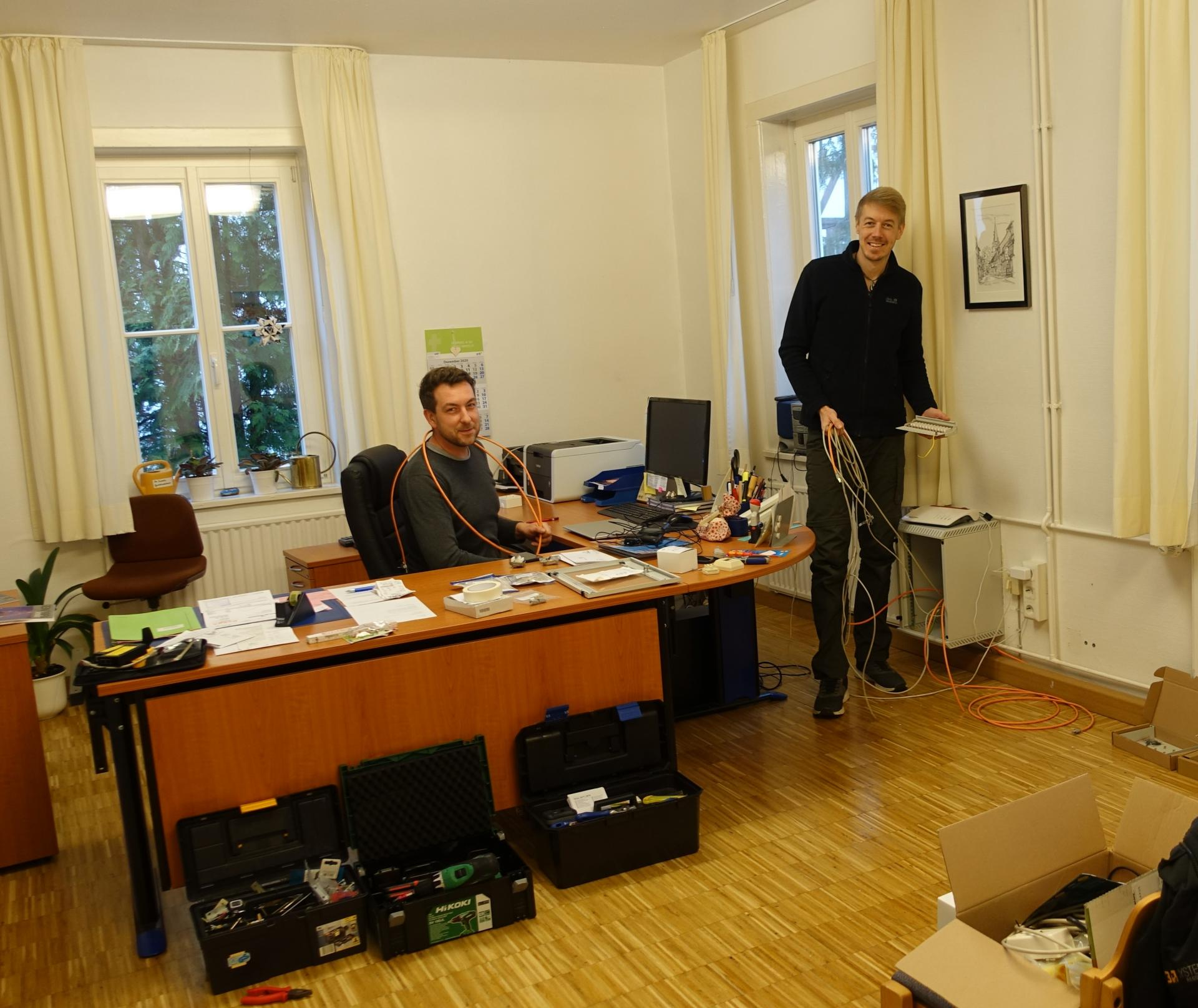 Timo Wiegreffe mit Benjamin Dippel, die im Gemeindebüro die Verkabelung per LAN/WLAN in den Kirchenraum aufrüsten.