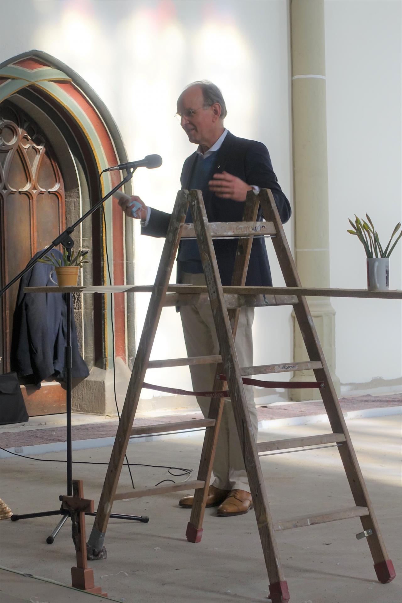 Landesbischof hinter dem 'Leiteraltar' mit Osterglocken und Kreuz am Fußpunkt