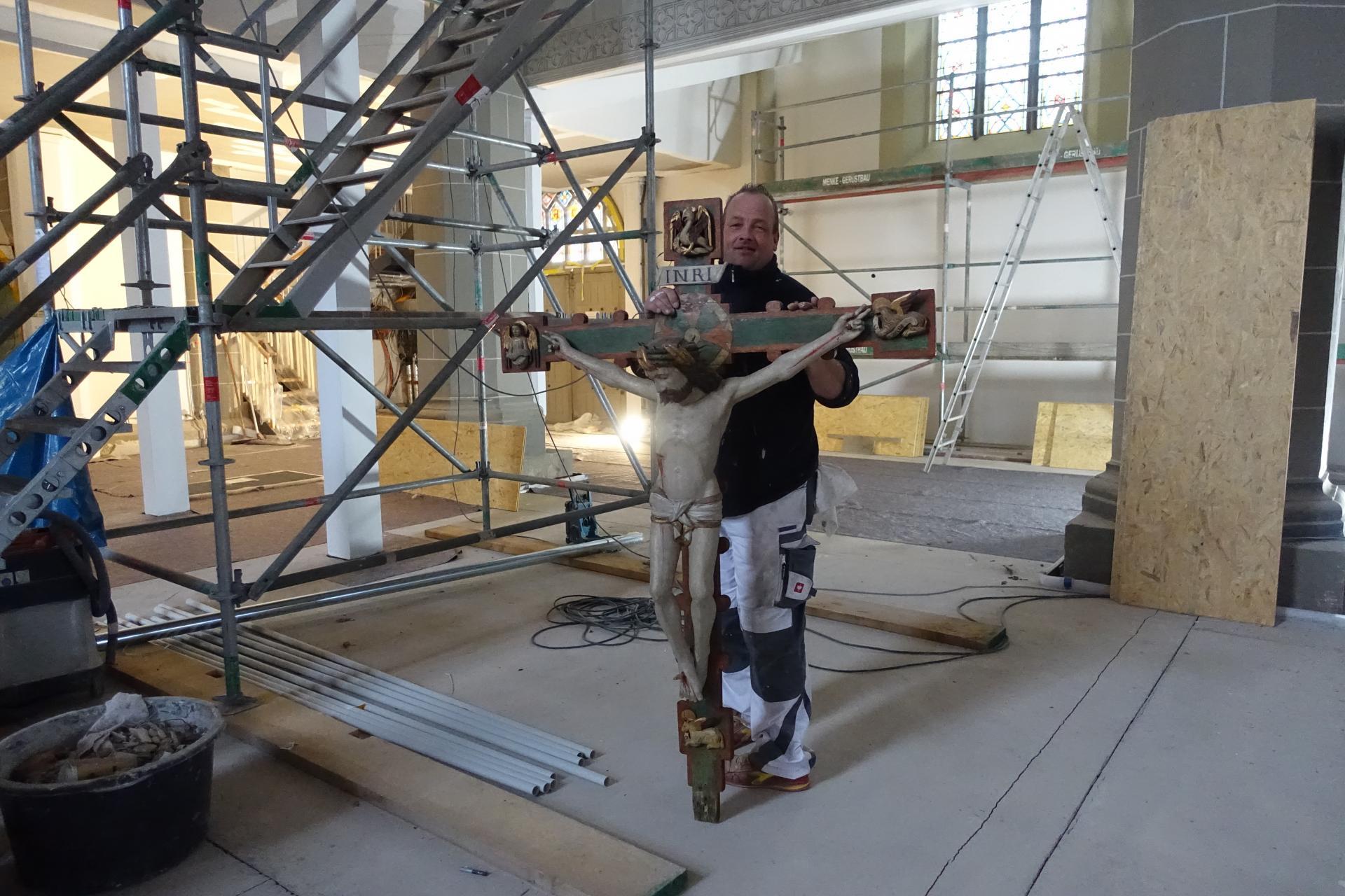 Maler Daniel Weinert mit dem 1,80 m großem Kreuz, das wir über das Emporengerüst etwas mühsam zur Erde brachten.