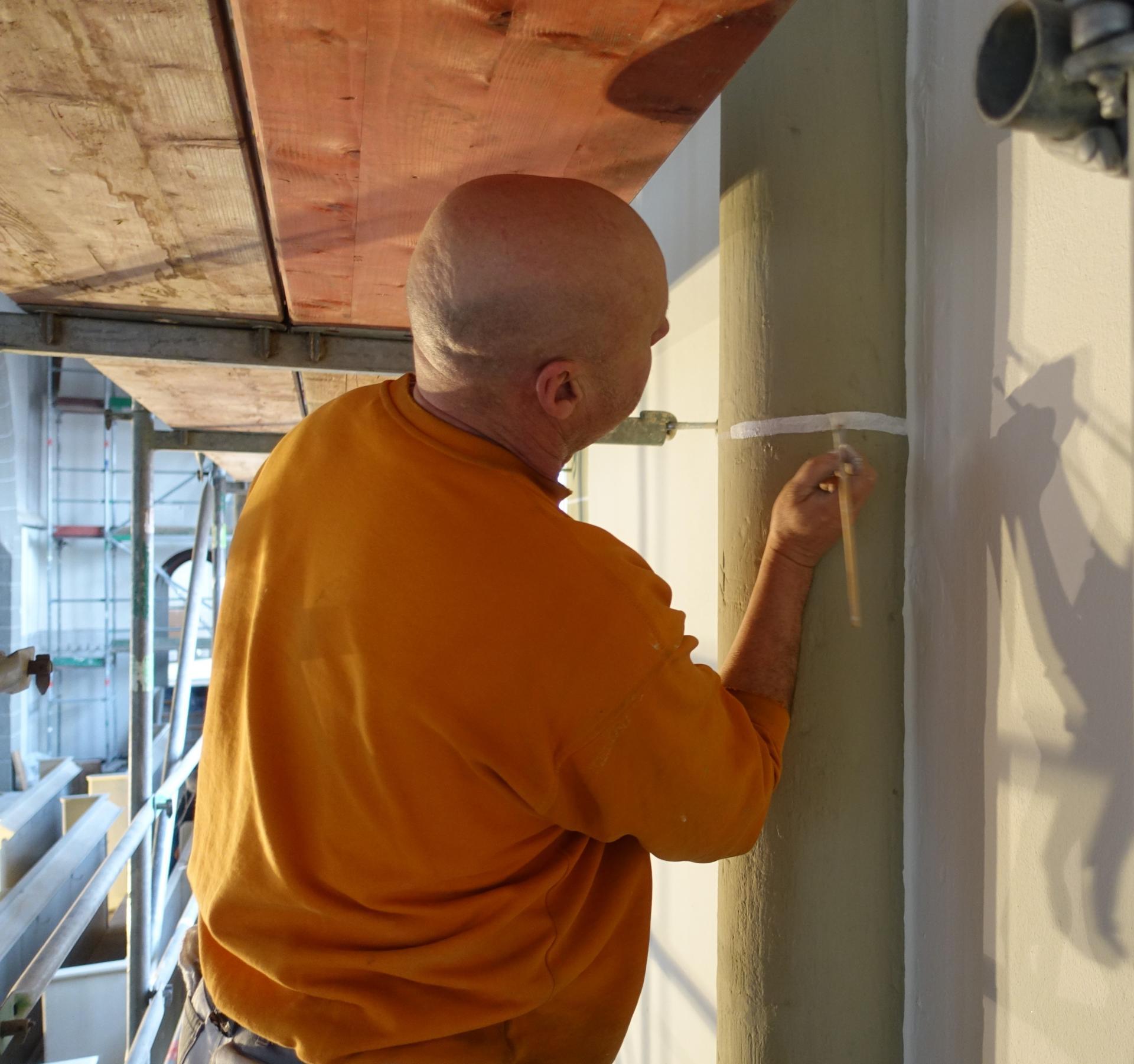 Dirk Alberding malt die Querstreifen an den Diensten mit freier Hand