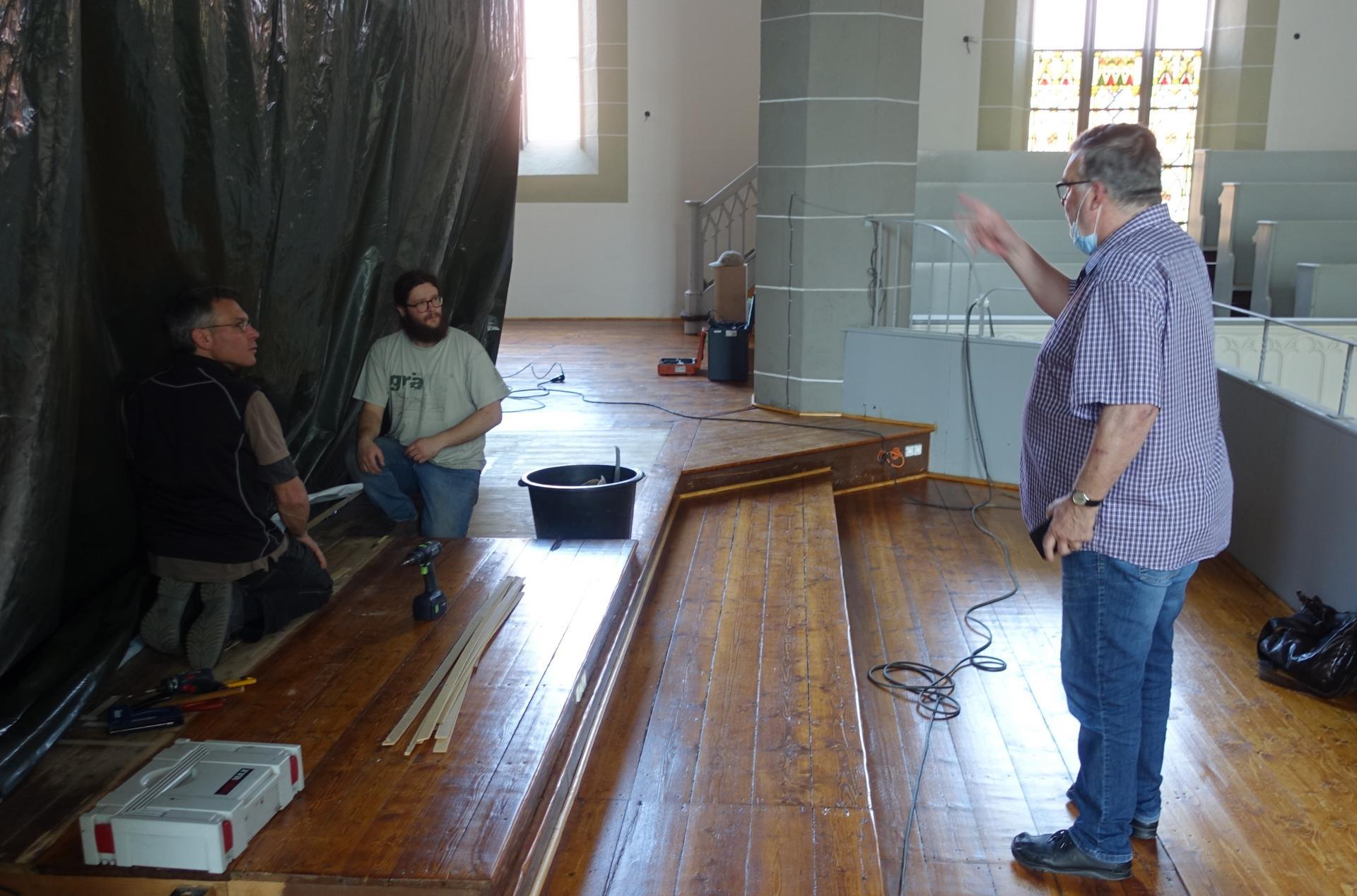 Frank Wagner, der uns als Architekt der Landeskirche großartig betreut, steht auf der neu lackierten Orgelempore- der erhobene Arm zeigt auf die Folie der Orgel und galt nicht als Mahnung an die Mitarbeiter der Orgelbauerfirma Bente
