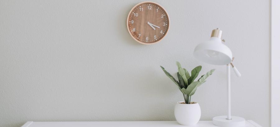 """Header-Bild """"Öffnungszeiten"""": Uhr, Schreibtisch, Pflanze, Tischlampe"""